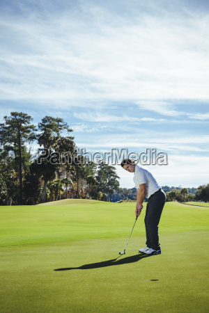 woman looking at man playing golf