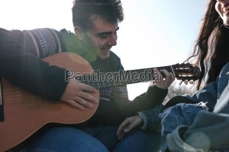 teenage boy playing guitar while sitting