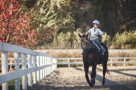 girl horseback riding in ranch