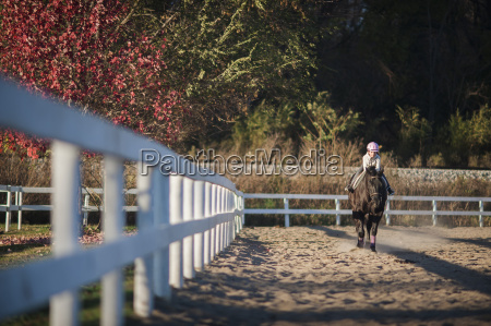girl riding horse in ranch