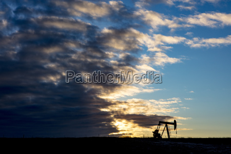mid distance view of silhouette pumpjack