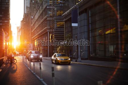 vehicles on street amidst modern buildings