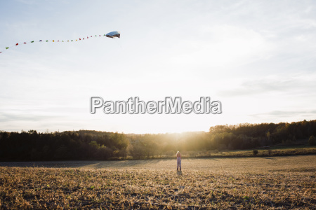 girl flying kite while standing on