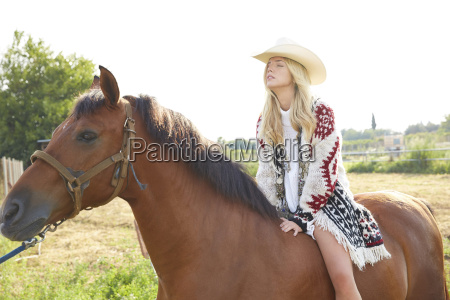 woman riding on horse in farm