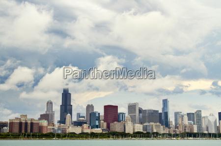 lake by modern buildings against cloudy
