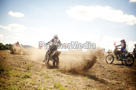 sportsmen riding dirt bike on field