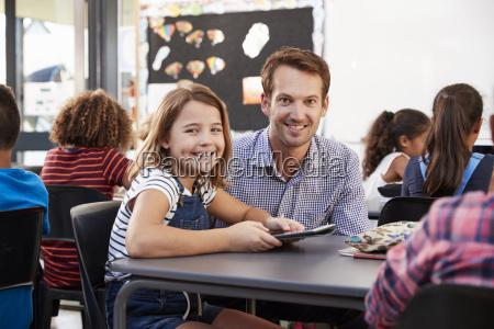 laerer og skolepige bruger tablet i