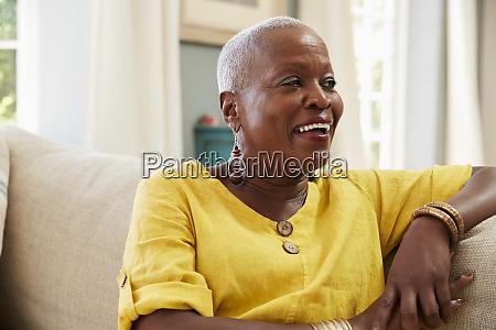 smiling senior woman sitting on sofa
