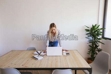 ung forretningskvinde staende ved skrivebordet ved