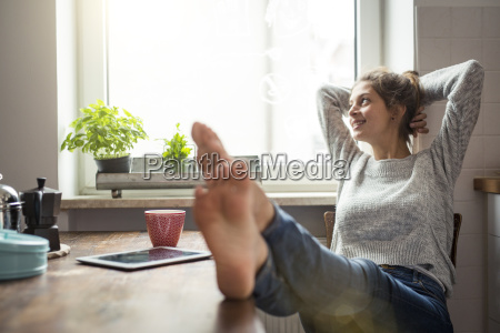 woman sitting at table in kitchen