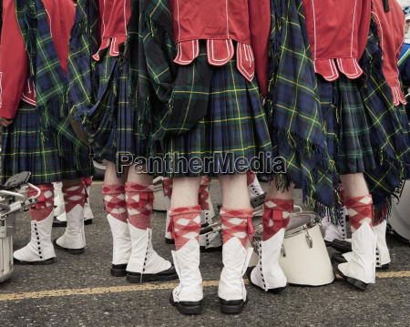 a group of people wearing kilts