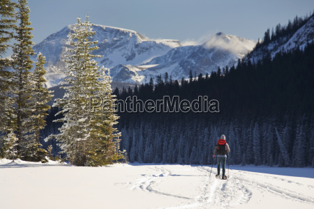 female snowshoeing on snow covered lake