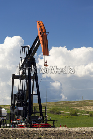 pumpjack with thunderstorm clouds and blue