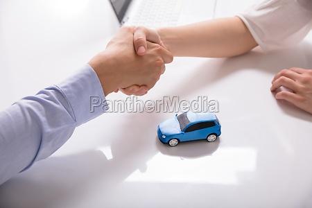 autohaendler schuettelt hand mit seinem mandanten