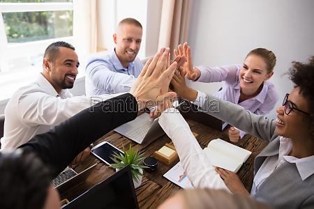 gruppe af glade unge forretningsfolk giver