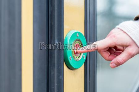 woman pressing door opener in train