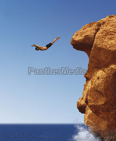 man diving from cliff into ocean