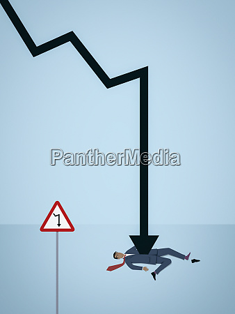 businessman impaled by decreasing line graph