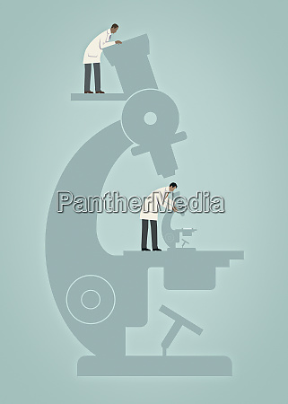 scientist with large microscope watching colleague