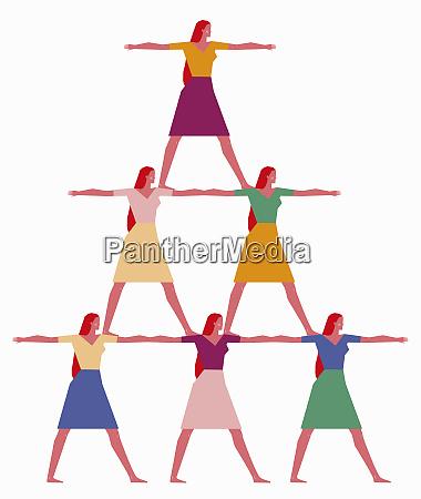 women forming human pyramid
