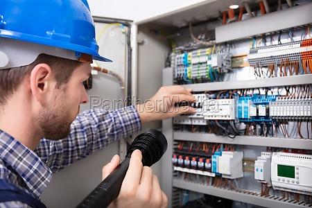elektriker undersoger en sikringskasse