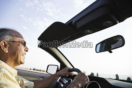an hispanic senior man laughing and