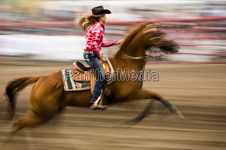 cowgirl riding horse during barrel race