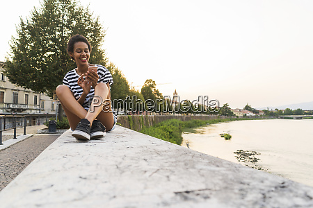 smiling young woman sitting on wall