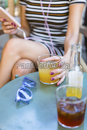 young woman sitting at pavement cafe