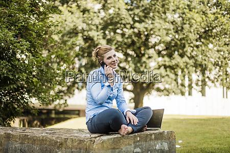 smiling woman sitting in urban park