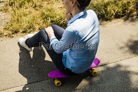 woman sitting on penny board talking