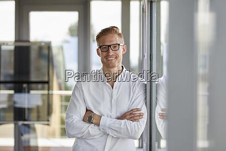 portraet af smilende forretningsmand i embedet