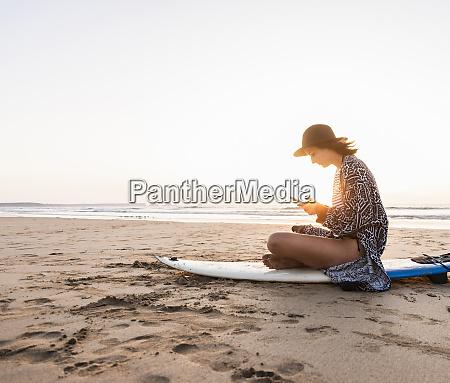 ung kvinde sidder pa surfbraet pa