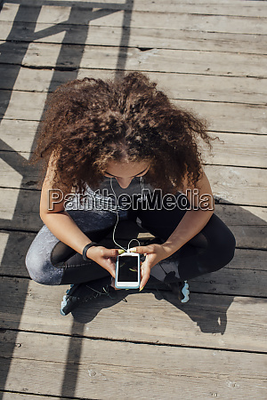 young athletic woman sitting on boardwalk