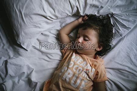 baby pige sover pa sengen med