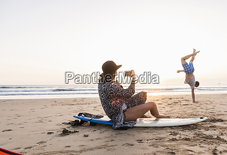 young woman sitting on surfboard taking