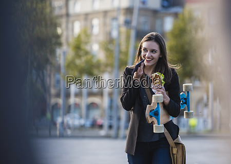 smiling young woman with longboard and