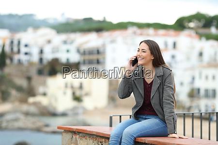 glad kvinde taler i telefon pa