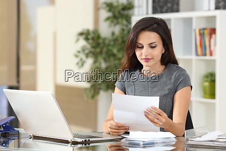 forretningskvinde der laeser et brev pa