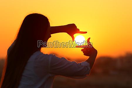 kvinde indramning sol med fingre ved
