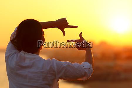 kvinde indramning med fingre ved solnedgang