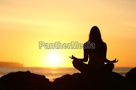 kvinde silhuet gor yoga ved solopgang