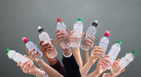forskellige mennesker holder vandflasker i traek