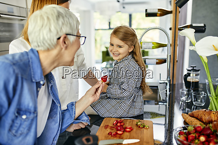grossmutter bietet stawberry zu enkelin mutter
