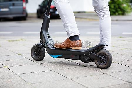 mand med el scooter staende pa