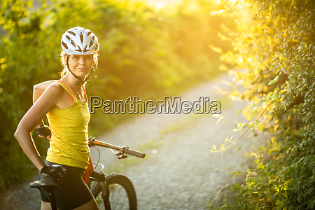 smuk ung kvinde cykling pa en