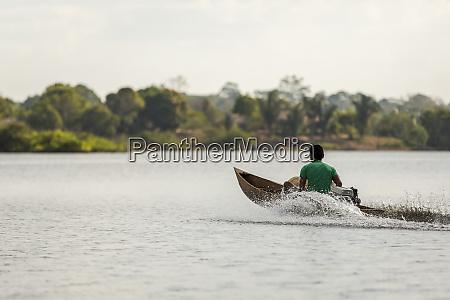 mand i en trae motoriseret kano