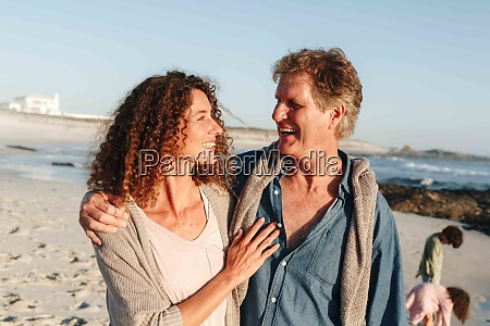 couple taking walk on sandy beach