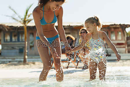 playful, mother, and, daughter, splashing, in - 27460530