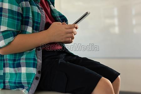 dreng sidder over skrivebordet og bruger